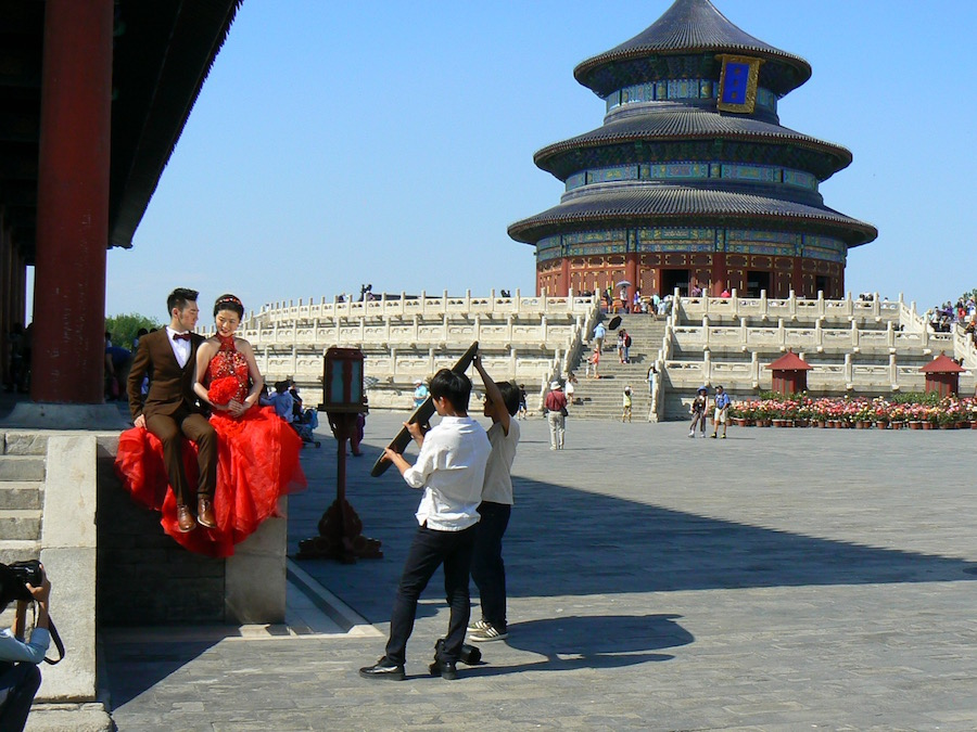 Chinese couples all over the world choose auspicious sites for their important wedding photographs. Here a couple, with the bride wearing the traditional, distinctive red dress, pose in front of Beijing's historic Temple of Heaven.