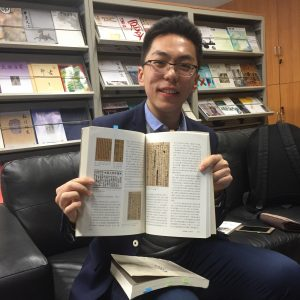 Graduate student Wei Haoyu holding one of his own published articles
