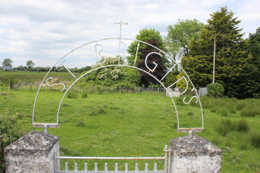 A sign marks St. Brigid's Well, Killare, County Westmeath. In order to access the holy well, which is located in a copse of trees, visitors must walk through a field of grazing sheep. Photograph taken by author on June 4, 2016.