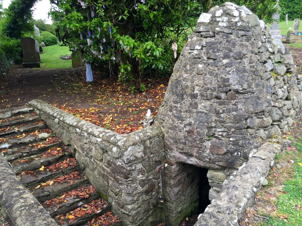 A stone beehive hut encloses St. Brigid's Well in Faughart, County Louth, and there are steep steps going down to the water. To the left of the well are clootie trees. Photograph taken by author on June 12, 2016.