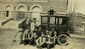 "College of St. Thomas students in front of Foley Theater posing with a ""Tin Lizzie."" ca. 1922"