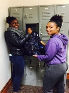 Library student workers Lorna Nakabuye and Sarah Kamba Binamu demonstrate the great feeling patrons get when their valuables are stored safely in a free locker at the library circulation desk.