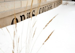 A sign marking the Opus College of Business is buried in snow on the Minneapolis Campus of the University of St. Thomas
