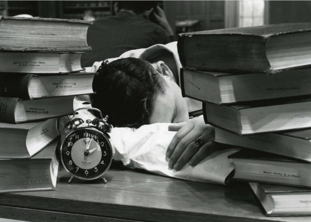 Student napping in library with pillow with stacks of books and an alarm clock