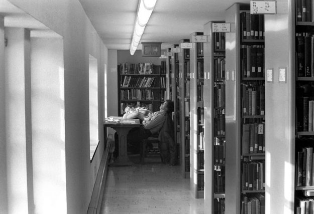 Black and white photo of two students sleeping by a window in the library stacks