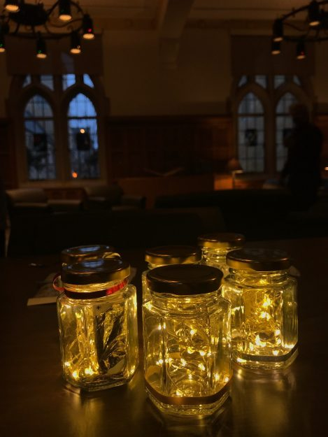 photo of small jars filled with tiny led lights. The room is dark except for the lights in the jars.