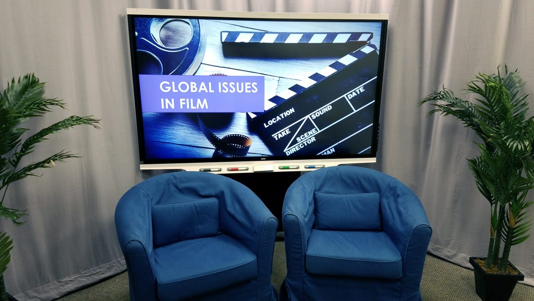 Image showing an example of the studio set up with the SMART Board lowered behind chairs displaying a backdrop of film and a title, two chairs and ferns