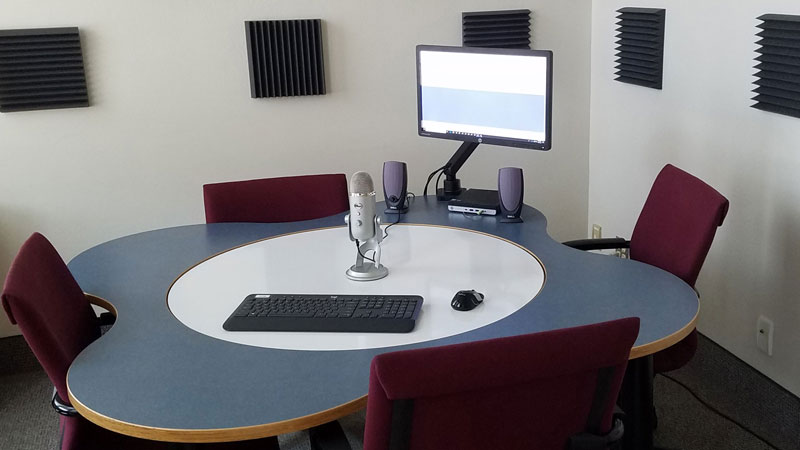 Podcast studio with microphone, table, and four chairs