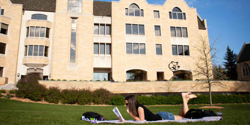 Student on blanket reading a book in the grass in front of O'Shaughnessy-Frey Library