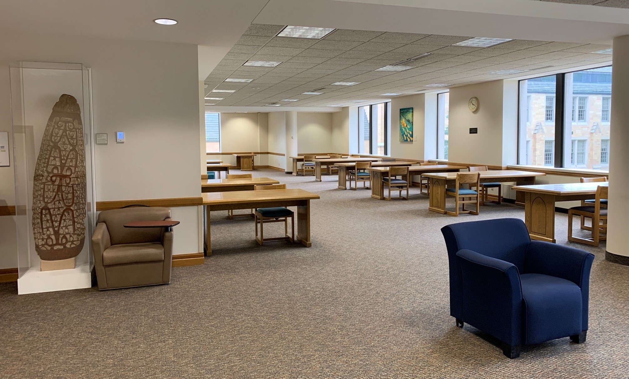 photo of study area on 2nd floor of OSF library. Tables and chairs are spaced out for safety