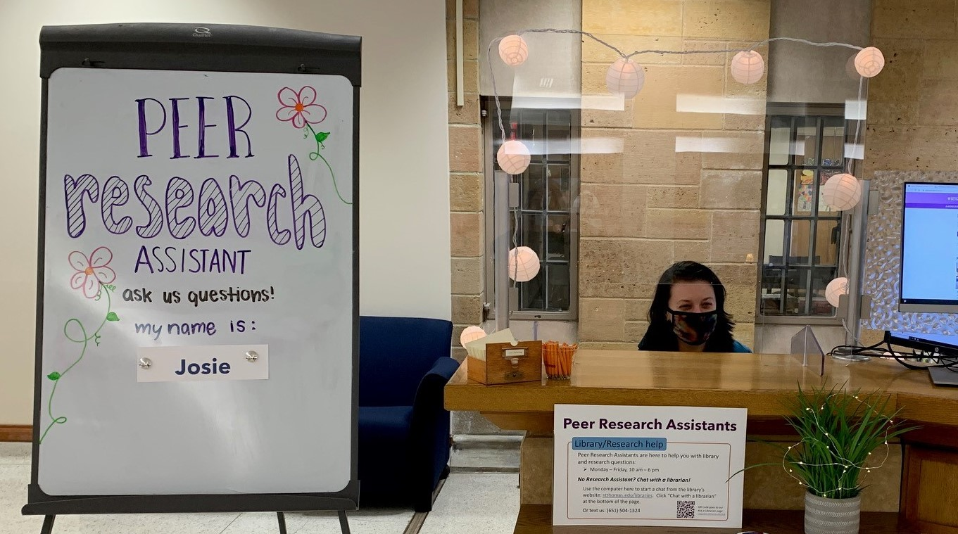 "A student sits behind a desk, the plexiglass barrier is decorated with lights. There is a white board that says ""Peer Research Assistants"" next to the desk"