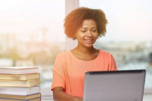 Black woman with natural hair in a peach-colored shirt looking at a laptop with a stack of books nearby.