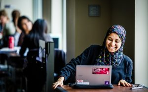 St Thomas student working at her laptop with a joyful expression