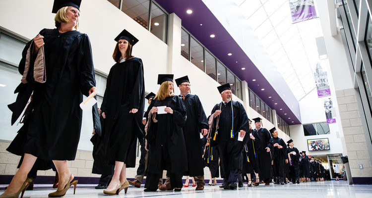 Students walk toward the graduate business commencement ceremony May 23, 2015 in the Anderson Athletic and Recreation Complex.