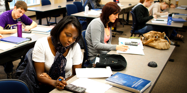 Olivia Mpanga (center) works on a math problem in her finance class March 13, 2012 in McNeely Hall. Felista and Olivia Mpanga, students from Uganda working to get their degrees from St. Thomas, were profiled for St. Thomas magazine.